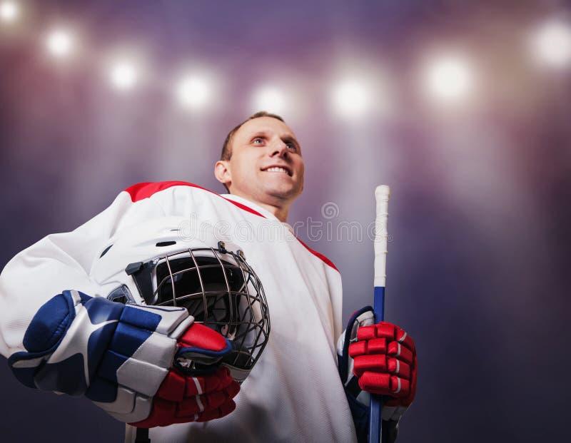Jogador de hóquei com o capacete nas mãos: momento da glória foto de stock