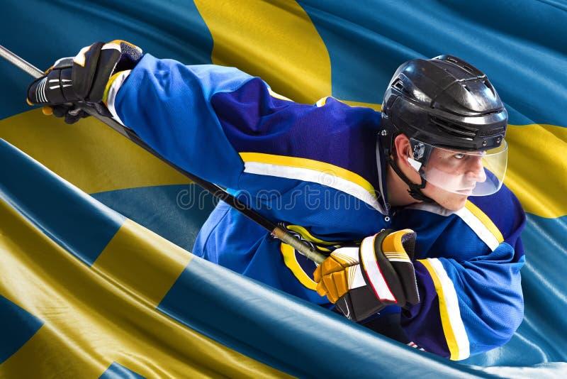 Jogador de hóquei da Suécia na ação em torno das bandeiras nacionais fotos de stock royalty free