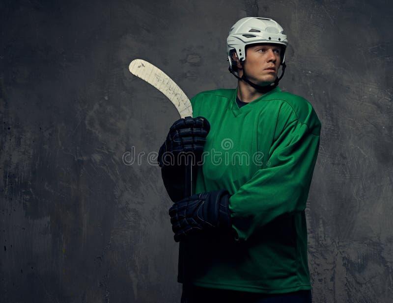 Jogador de hóquei que veste a engrenagem protetora verde e o capacete branco que estão com a vara de hóquei em um fundo cinzento imagem de stock