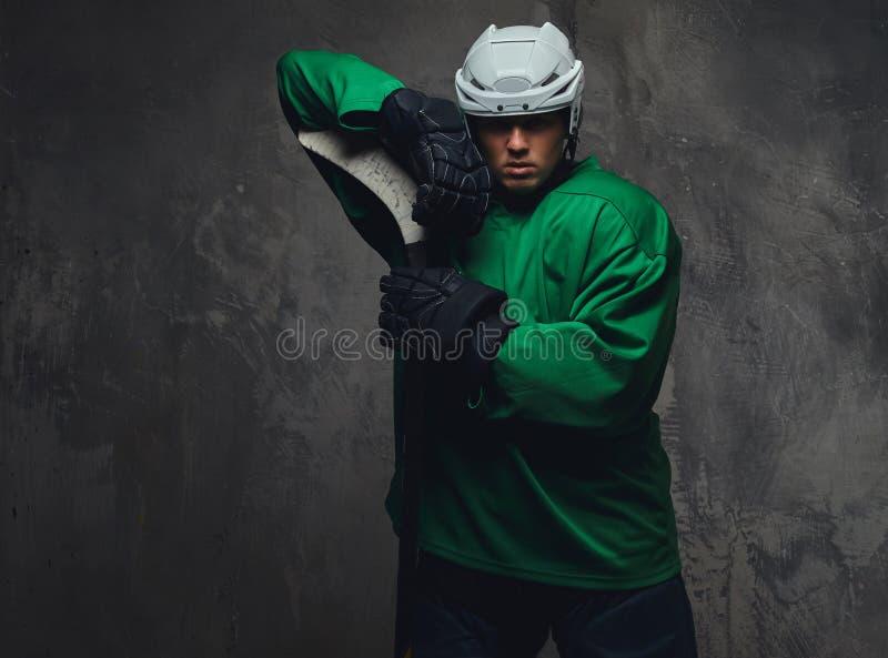 Jogador de hóquei que veste a engrenagem protetora verde e o capacete branco que estão com a vara de hóquei em um fundo cinzento imagem de stock royalty free