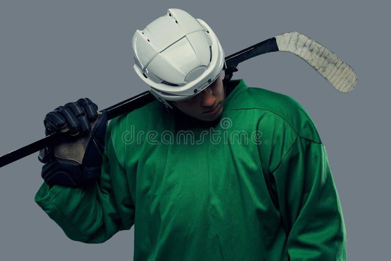 Jogador de hóquei que veste a engrenagem protetora verde e o capacete branco que estão com a vara de hóquei isolado em um cinza imagens de stock
