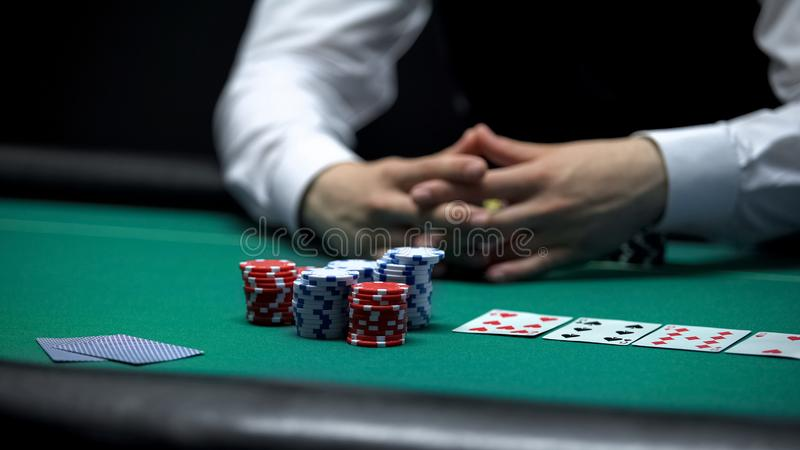 Jogador de pôquer do cliente do casino que faz a aposta com todas as microplaquetas, possibilidade ganhar no jogo fotos de stock