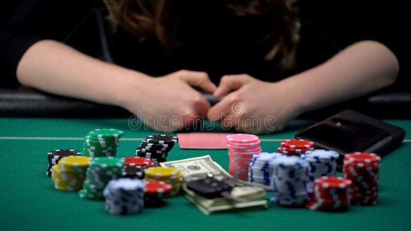 Jogador de pôquer fêmea que aposta todas as microplaquetas, dinheiro e chaves da casa no jogo do casino fotografia de stock