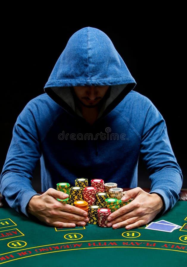 Jogador de pôquer que toma microplaquetas de pôquer após o vencimento fotos de stock