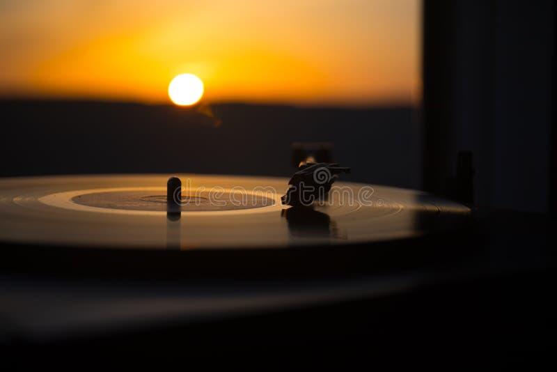 Jogador de registro do vinil da plataforma giratória no fundo de um por do sol sobre as montanhas Tecnologia sadia para que o DJ  fotos de stock royalty free