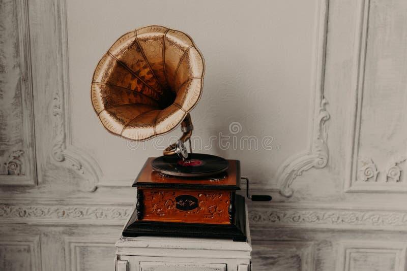 Jogador de registro idoso contra a parede de madeira antiga Gramophon antigo fotos de stock royalty free