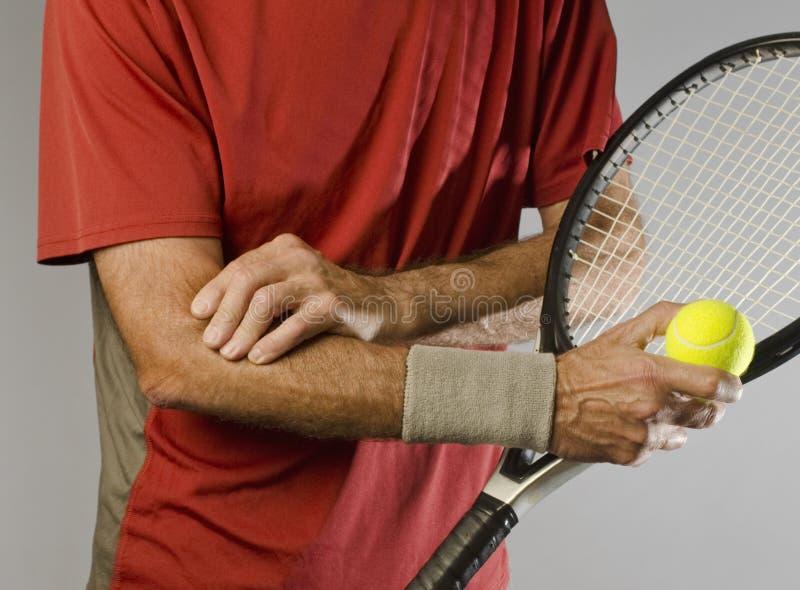 Jogador de ténis que faz massagens o cotovelo foto de stock