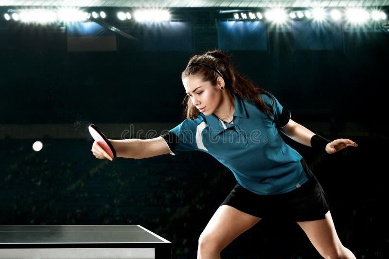 Jogador de tênis considerável novo da mulher no jogo no fundo preto Tiro da ação imagens de stock