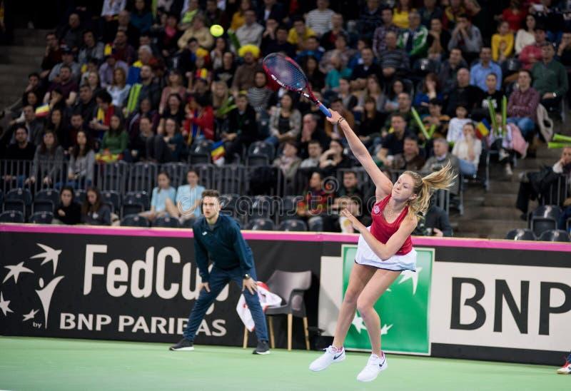 Jogador de tênis da mulher que bate a bola com raquete fotos de stock royalty free