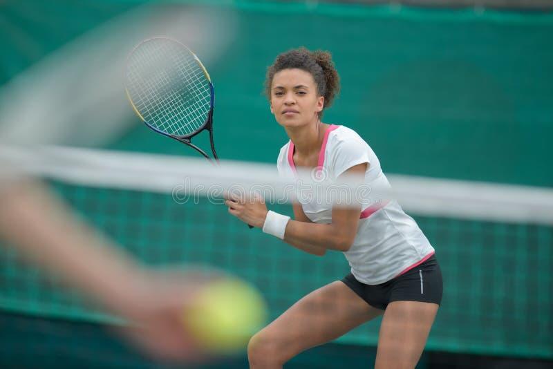 Jogador de tênis fêmea bonito na ação fotografia de stock royalty free