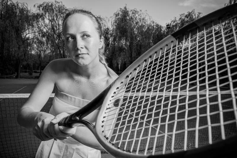 Jogador de tênis fêmea que guarda a raquete na imagem preto e branco imagens de stock royalty free