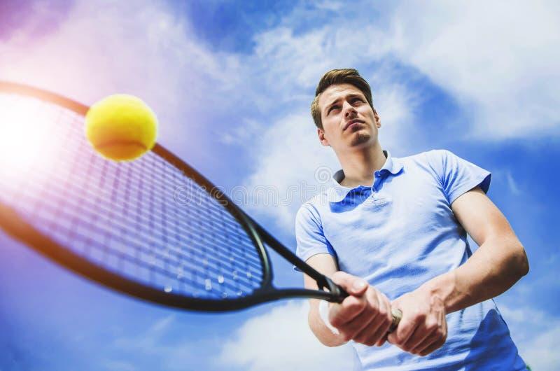 Jogador de tênis feliz pronto para bater a bola com raquete fotos de stock