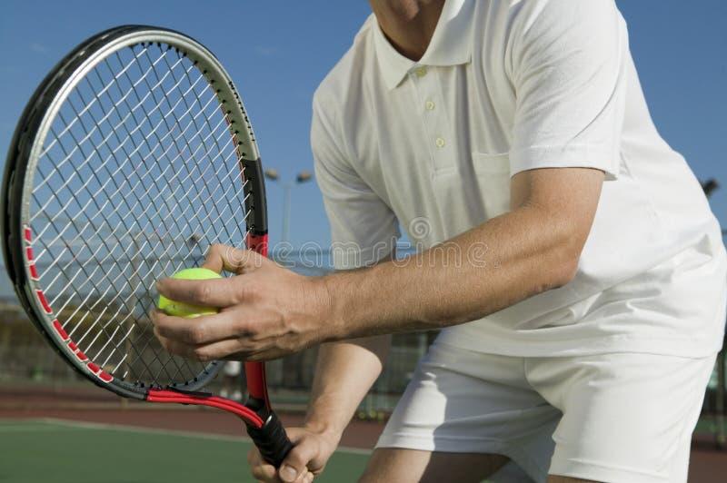 Jogador de tênis masculino que prepara-se para servir a opinião de baixo ângulo meados de da seção imagens de stock royalty free