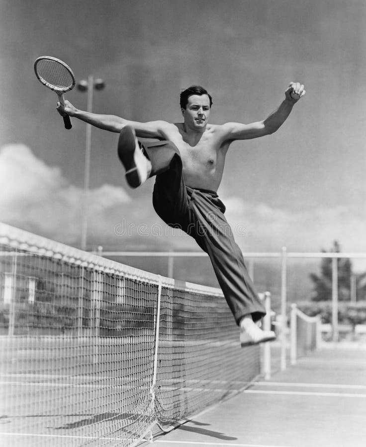 Jogador de tênis masculino que salta sobre a rede (todas as pessoas descritas não são umas vivas mais longo e nenhuma propriedade foto de stock royalty free