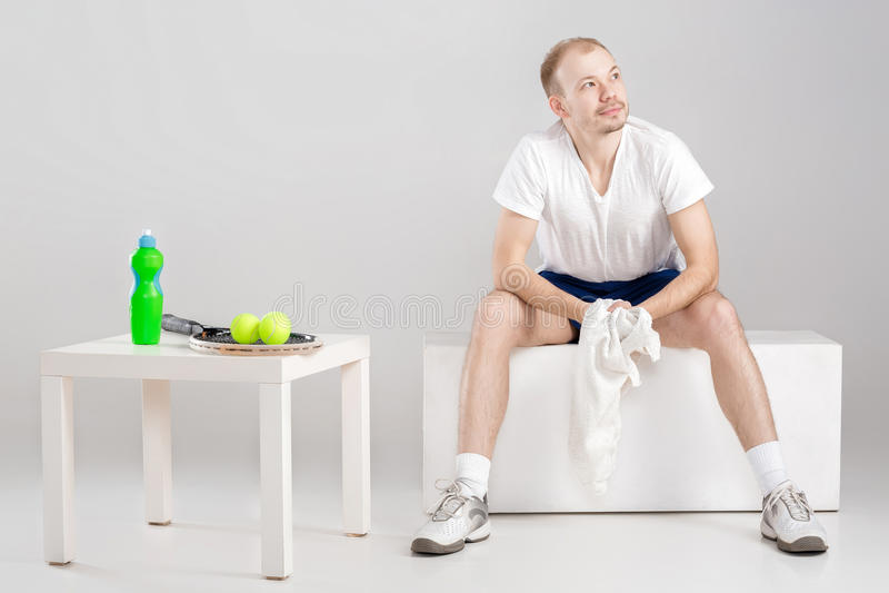 Jogador de tênis novo com a toalha que descansa após o exercício fotografia de stock