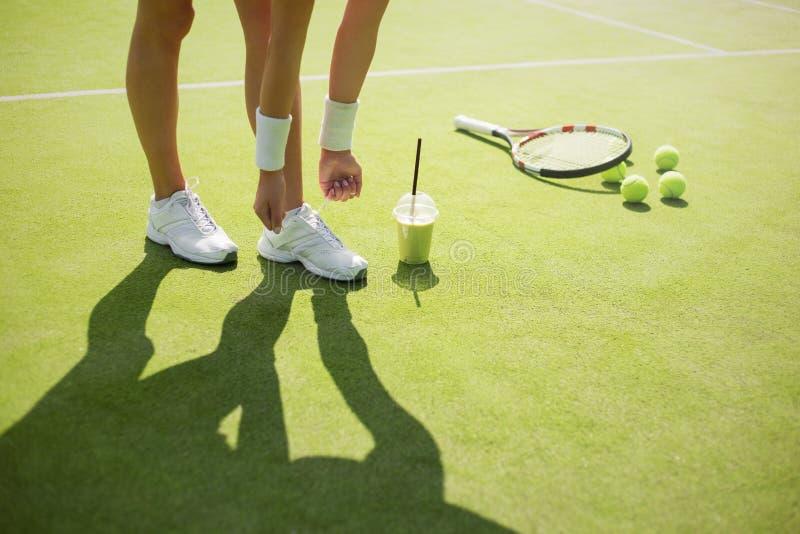 Jogador de tênis que amarra sapatas dos esportes antes da prática imagens de stock