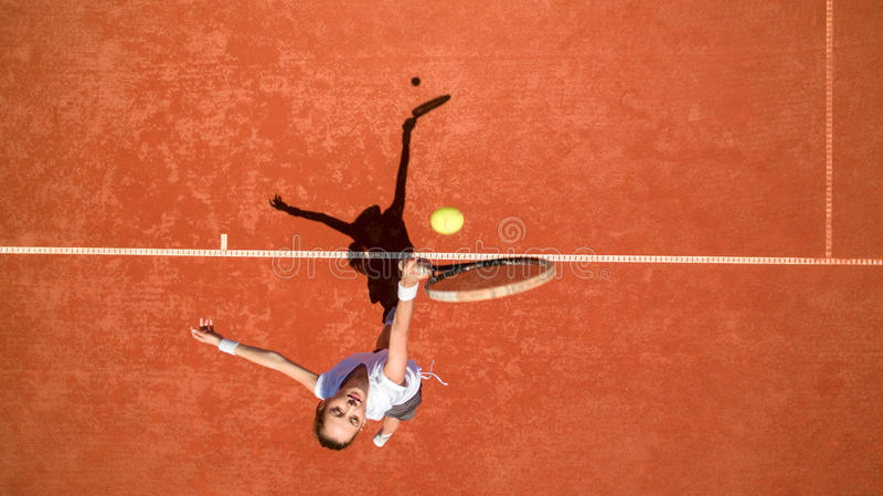 Jogador de tênis que bate a bola no terreno do tênis foto de stock