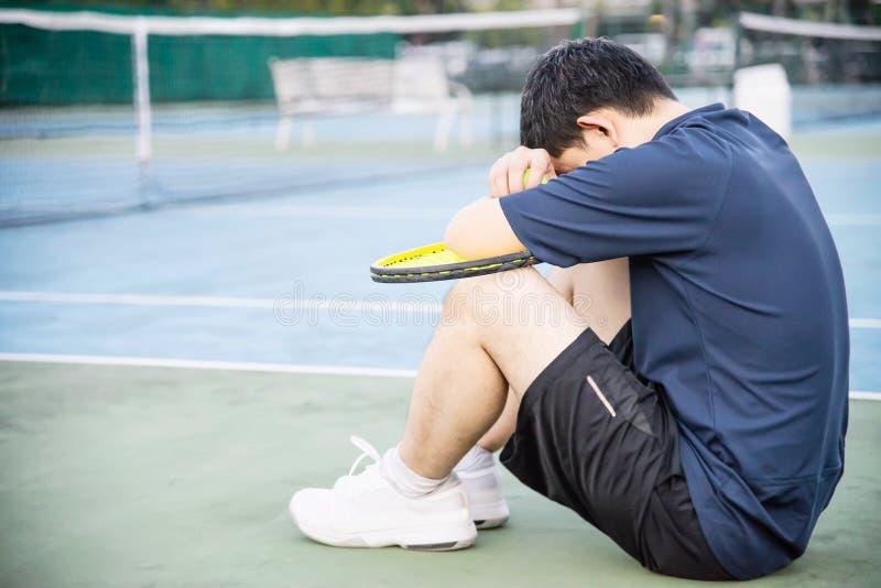 Jogador de tênis triste que senta-se na corte após para perder um fósforo fotografia de stock