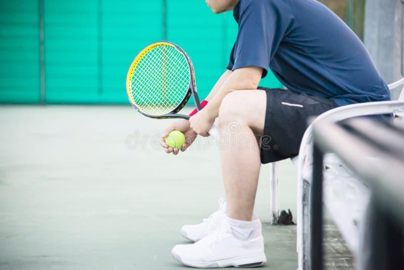 Jogador de tênis triste que senta-se na corte após para perder um fósforo fotografia de stock royalty free