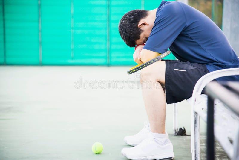Jogador de tênis triste que senta-se na corte após para perder um fósforo imagens de stock