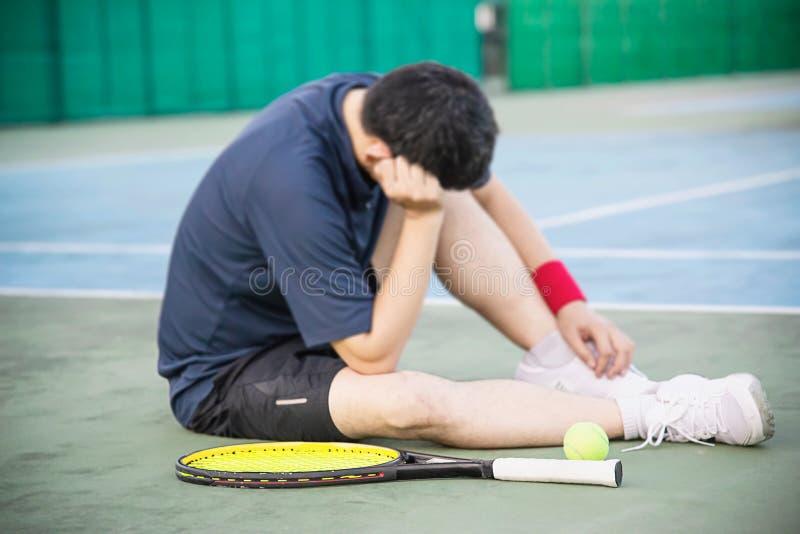 Jogador de tênis triste que senta-se na corte após para perder um fósforo imagem de stock royalty free