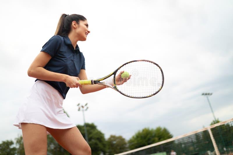 Jogador de t?nis da mulher que sorri ao guardar a raquete durante o f?sforo do t?nis imagem de stock