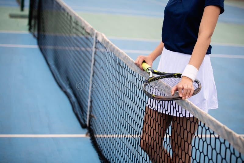 Jogador de t?nis da mulher que sorri ao guardar a raquete durante o f?sforo do t?nis fotografia de stock