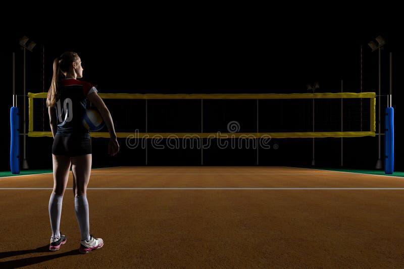 Jogador de voleibol fêmea que está com a bola da salva foto de stock royalty free
