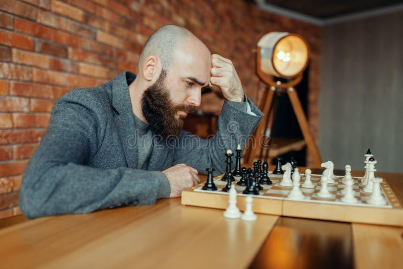 Jogador de xadrez masculino que joga, processo de pensamento fotos de stock royalty free