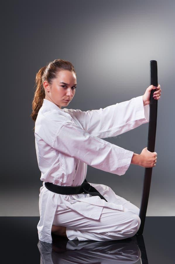 Jogador fêmea novo bonito do karaté que levanta com a espada no fundo cinzento fotografia de stock royalty free