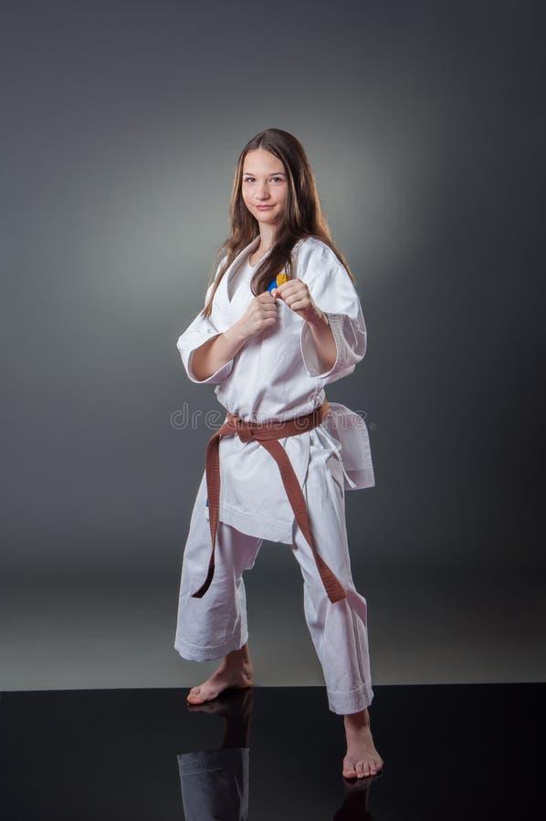 Jogador fêmea novo bonito do karaté que levanta no fundo cinzento fotos de stock