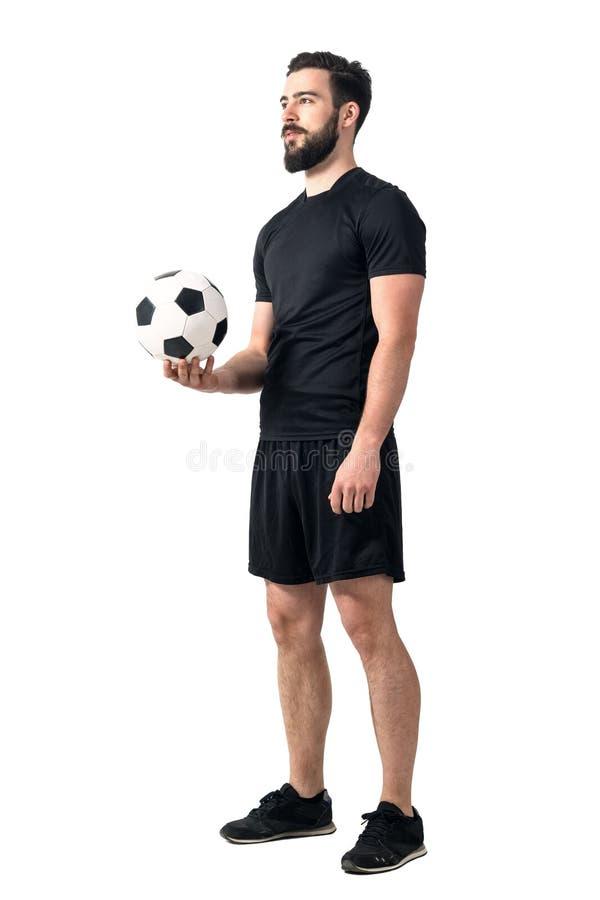 Jogador futsal do futebol ou do futebol que guarda a bola em uma mão que olha acima foto de stock royalty free