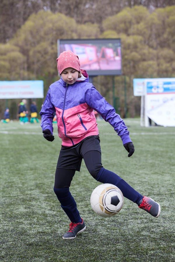 jogador novo que corre com a bola no campo de grama artificial, menina preteen do futebol Esquerdo-equipado com pernas fotos de stock royalty free