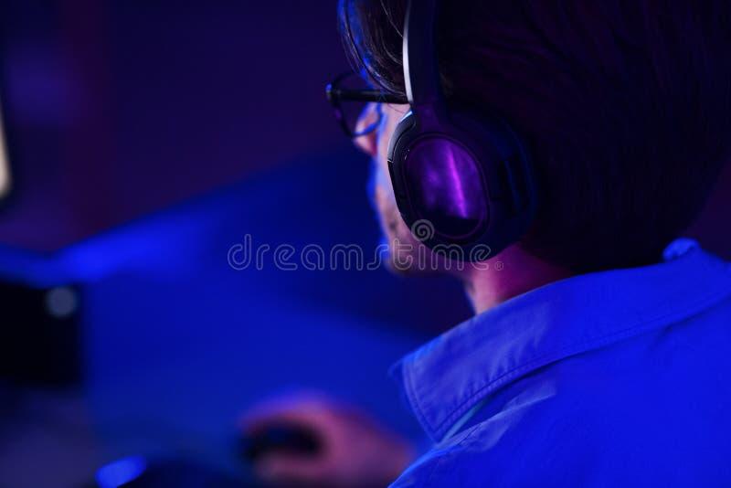 Jogador usando headset e jogando videogame online imagem de stock royalty free