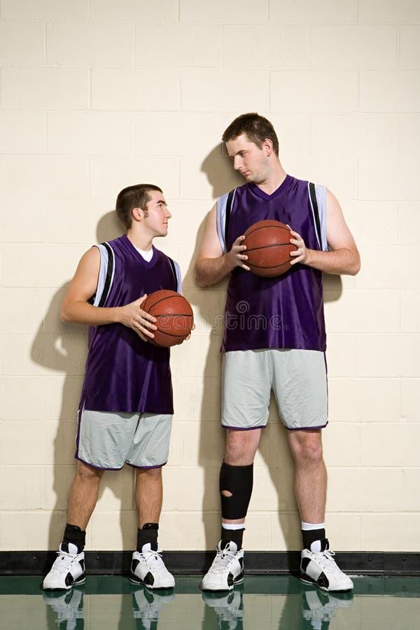 Jogadores de basquetebol altos e curtos fotografia de stock royalty free