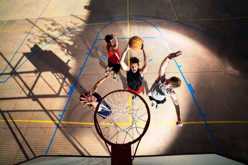 Jogadores de basquetebol novos que jogam com energia imagens de stock