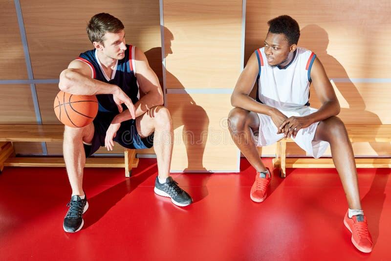 Jogadores de basquetebol que sentam-se em bancos imagem de stock