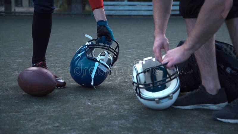 Jogadores de futebol americano que preparam capacetes imagem de stock
