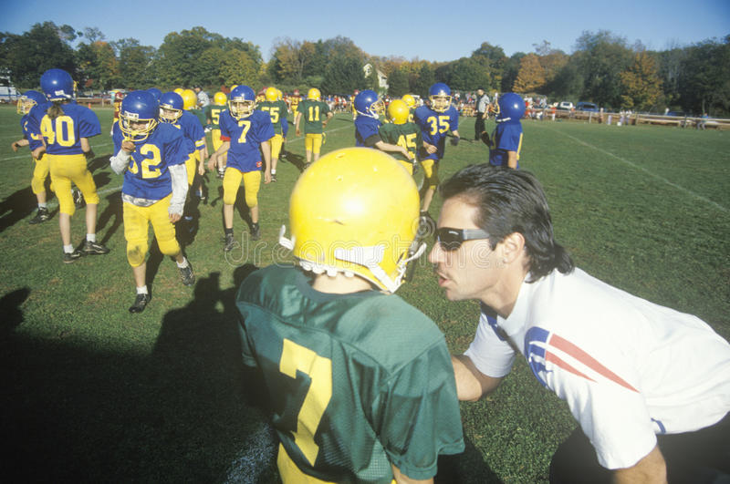 jogadores de futebol da Micro-liga, envelhecidos 8 a 11 com o treinador durante o jogo, Plainfield, CT imagem de stock