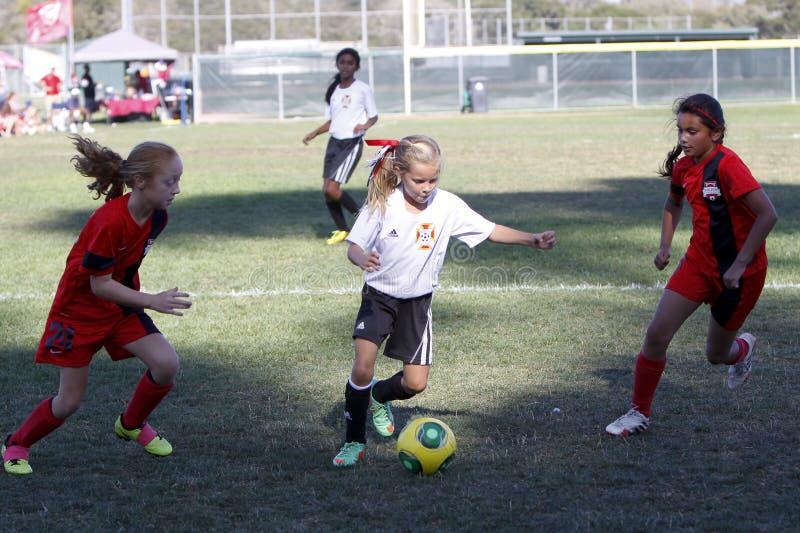 Jogadores de futebol do futebol da juventude das meninas que correm para a bola fotografia de stock