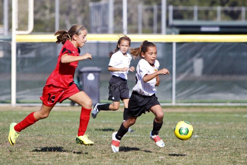 Jogadores de futebol do futebol da juventude das meninas que correm para a bola foto de stock