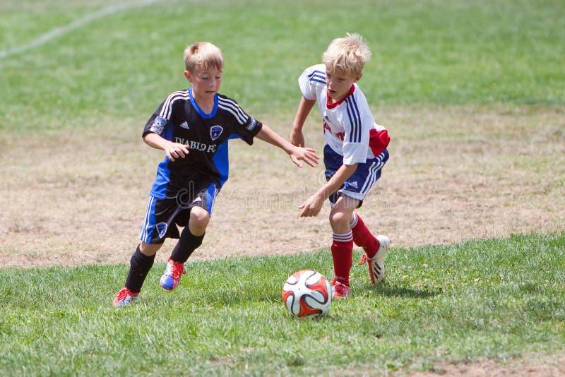 Jogadores de futebol do futebol da juventude que correm com a bola imagem de stock royalty free