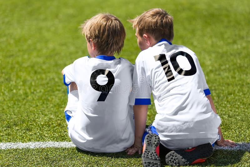 Jogadores de futebol novos do futebol Rapazes pequenos que sentam-se no passo do futebol fotos de stock royalty free