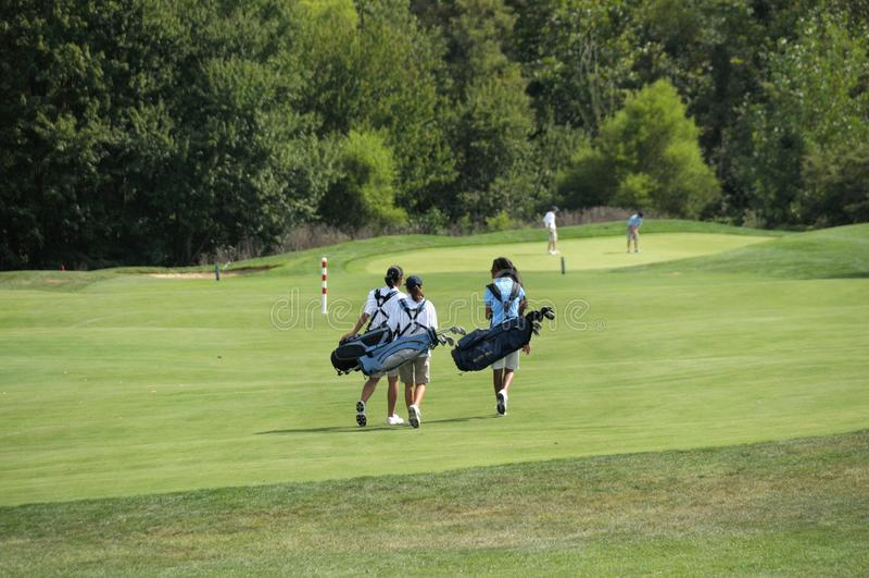 Jogadores de golfe adolescentes que andam a seu furo seguinte no golfe fotos de stock