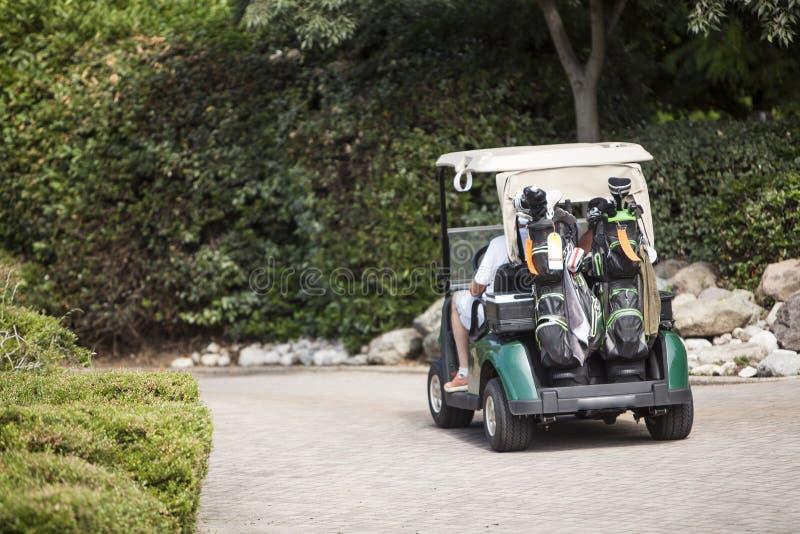 Jogadores de golfe dos pares no golfe do carro imagem de stock royalty free