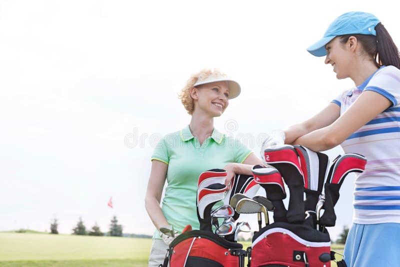 Jogadores de golfe fêmeas felizes que falam no campo de golfe contra o céu claro imagens de stock royalty free