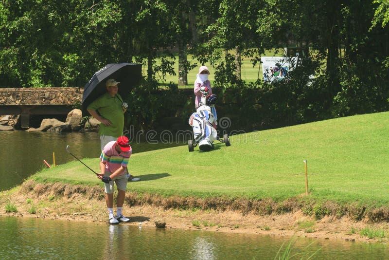 Jogadores de golfe no campo de golfe em Tailândia foto de stock