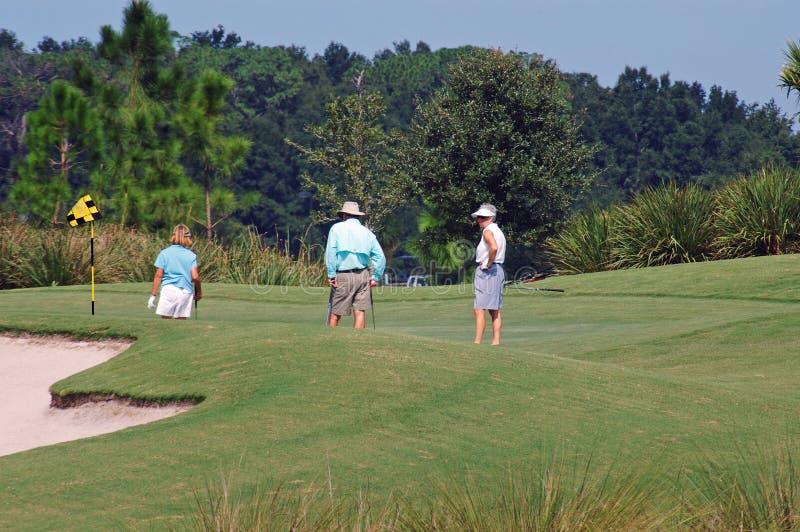 Jogadores de golfe no verde fotos de stock royalty free