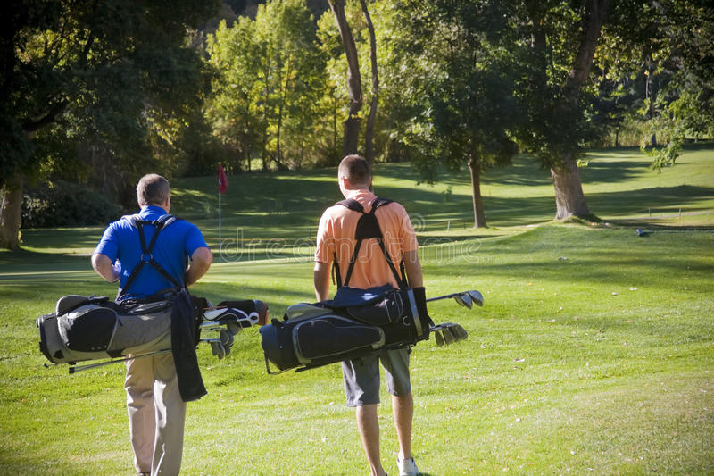 Jogadores de golfe que andam no campo de golfe imagens de stock royalty free