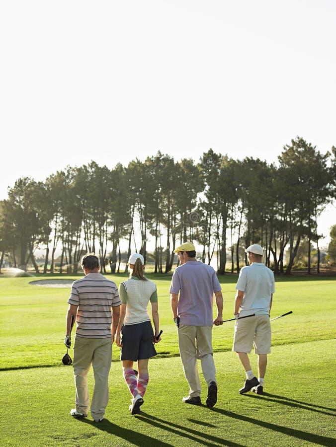 Jogadores de golfe que andam no campo de golfe fotografia de stock royalty free